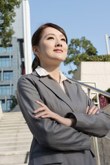 Confident Asian business woman standing in outside of office in
