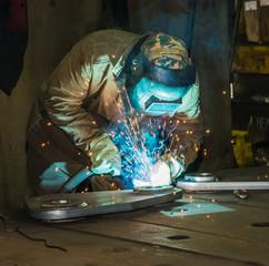 Сварщик за работой в ослепительном свете ярких брызг  металла.
