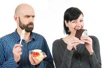 Mann mit Obst schaut böse zu Schokolade essender Frau