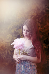beautiful girl with pink peony in hand