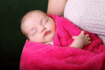 baby wrapped in a pink blanket on hands at mum