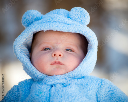 Cute infant baby boy wearing fluffy snow suit during winter
