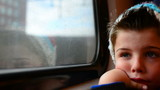boy on a train, next to a window