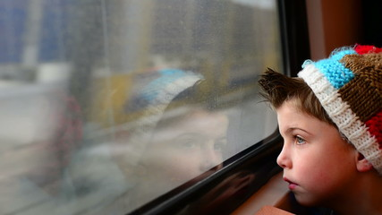 boy on a train, next to window
