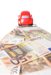 red toy car running on a road of euro bank notes