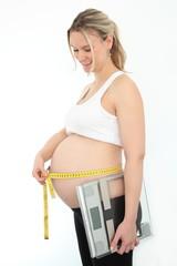 Schwangere Frau mit Massband und Waage