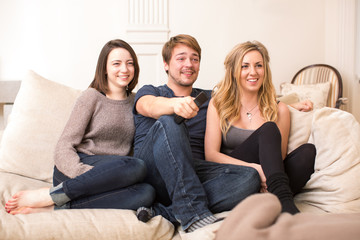 Three teenage friends sitting watching television