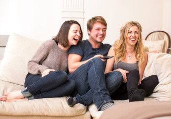 Three teenagers enjoy a funny television program