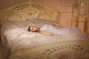 Young elegant girl lying on the bed