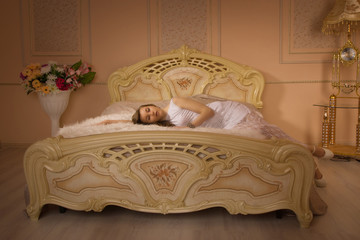Young girl on the bed in an elegant bedroom