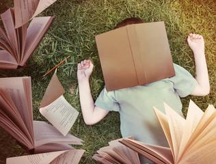 Flying Books Around Sleeping Boy in Grass