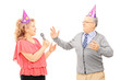 Middle aged couple with party hats dancing and singing