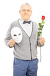 Middle aged gentleman holding rose flower and mask