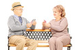 Senior couple playing cards seated on wooden bench