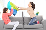Two young girls having a pillow fight on sofa, at home