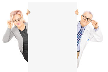 Middle aged woman and male doctor standing behind blank panel