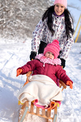 Mother sledding a small child on a sled in the winter.
