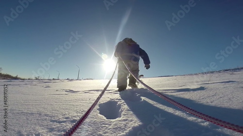 Little kid pulling sled to the slope top