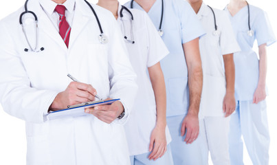 Doctor Standing In Group Writing Prescription