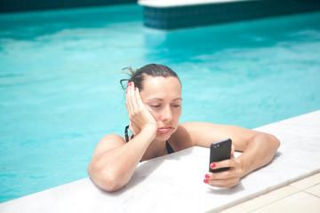 Frau mit Handy gestresst am Pool