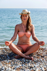 Trendy young woman meditating on the beach