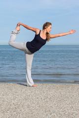 Beautiful woman doing yoga at the seaside