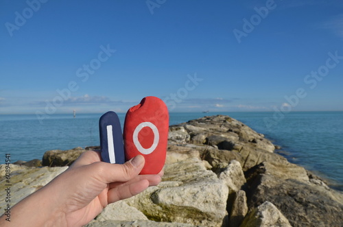 Io, egoism on stones with sea background