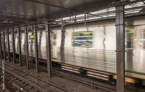 Silver Train speeding up on a subway station interior