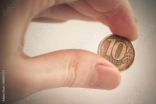 Coin in hand - ten rubles. Color toned image.