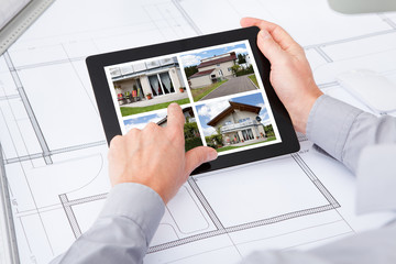 Digital Tablet Over Blueprint Browsing Pictures Of House