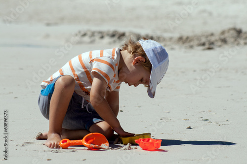 A little boy is preparing to build a sand castle on a beach
