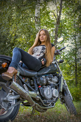 girl posing on a motorcycle on the background of nature