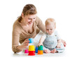 kid girl and mother play together with cup toy