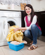 happy brunette woman doing laundry