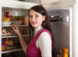 woman searching for something in refrigerator