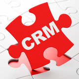 Business concept: CRM on puzzle background