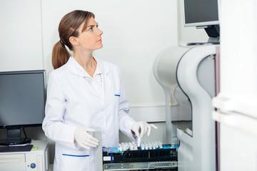 Scientist Loading Coagulation Analyzer With Test Samples