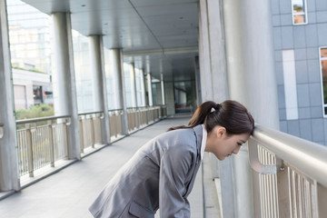 Tired Asian business woman put head on balustrade