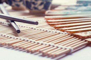 Chopsticks lying on a reed mat