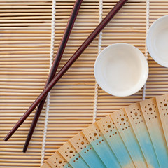 Chopsticks and porcelain cups on a reed mat