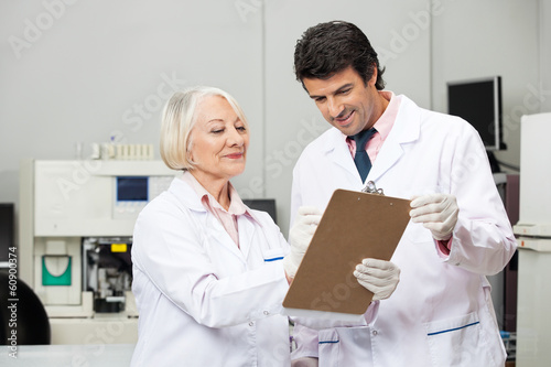 Scientists Writing On Clipboard In Laboratory