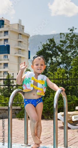 Happy little boy waving at the camera poolside
