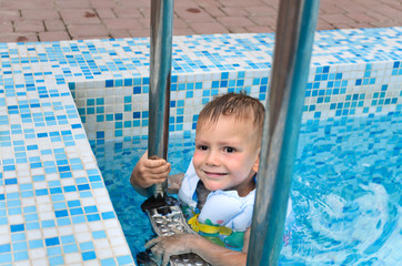 Cute little boy enjoying a swim in a pool