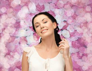 beautiful woman spraying pefrume on her neck