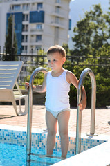 Cute little boy standing on swimming pool steps