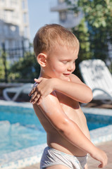 Little boy applying suntan lotion to his skin