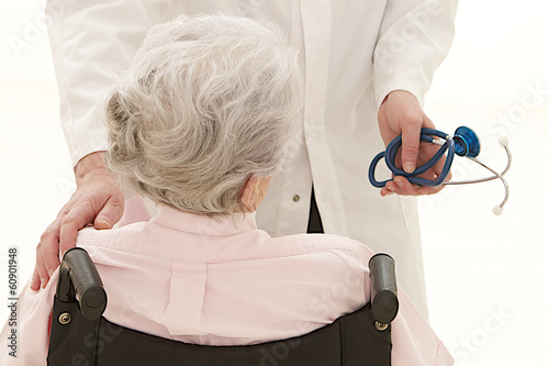 caring doctor with disabled  senior patient back view