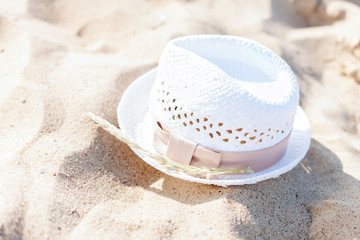 white straw hat lying in the sand on the beach