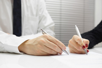 business partners signing a document