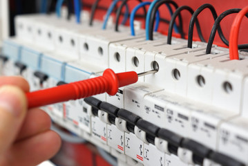 Hand of an electrician with multimeter probe at an electrical sw